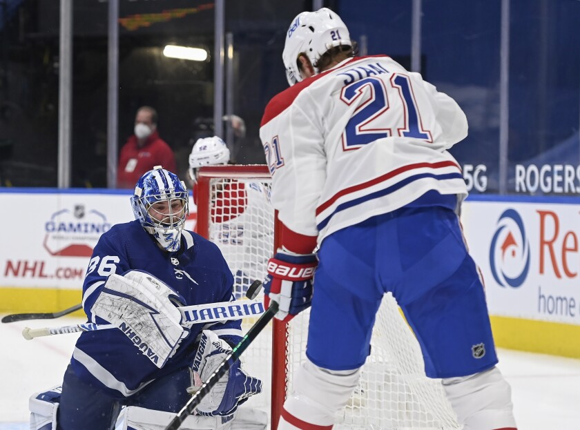 Toronto Maple Leafs goaltender Jack Campbell (36) bats the puck out of the air as Montreal Canadiens forward Eric Staal (21) keeps close during the second period of an NHL hockey game Wednesday, April 7, 2021, in Toronto. (Nathan Denette/The Canadian Press via AP)