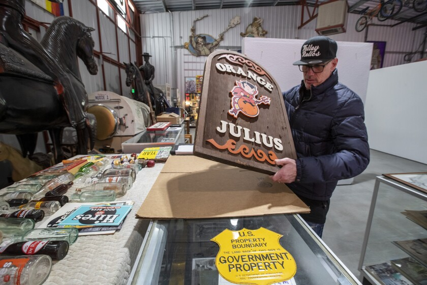 A man with a collection of vintage signs