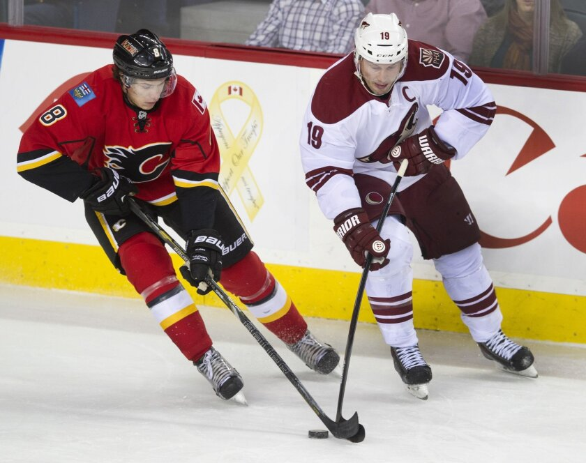 Phoenix Coyotes' Shane Doan, right, battles for the puck with Calgary Flames' Joe Colborne during the first period of an NHL hockey game, Wednesday, Dec. 4, 2013 in Calgary, Alberta. (AP Photo/The Canadian Press, Larry MacDougal)