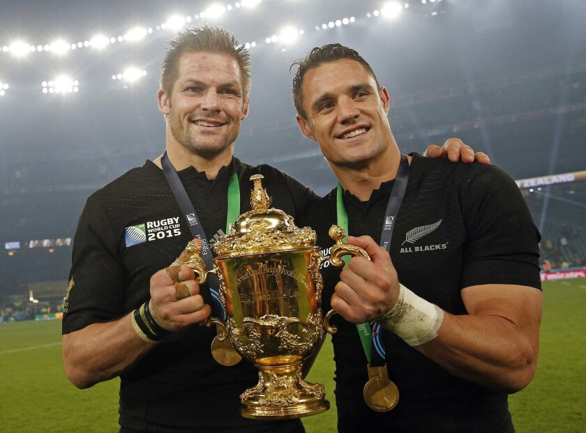 New Zealand's captain Richie McCaw, left, and Dan Carter hold the trophy aloft after the Rugby World Cup final between New Zealand and Australia at Twickenham Stadium in London,  Saturday, Oct. 31, 2015.  The All Blacks won 34-17. (AP Photo/Christophe Ena)
