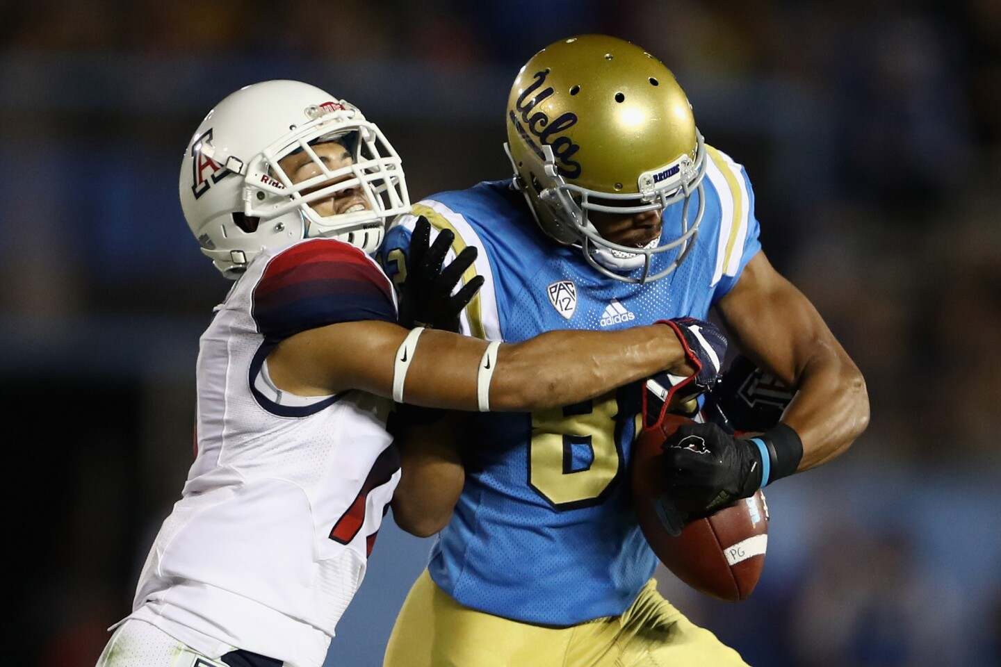 Arizona defensive back Jace Whittaker strips the ball from UCLA receiver Eldridge Massington during the first half.