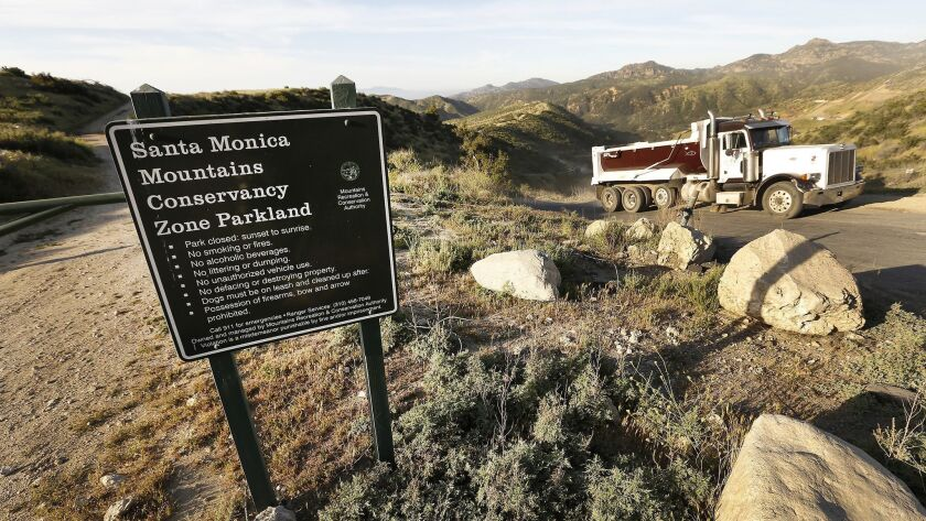 Trucks depart after disposing of a load of fill at Wayne Fishback's ranch in Browns Canyon above Chatsworth last April.
