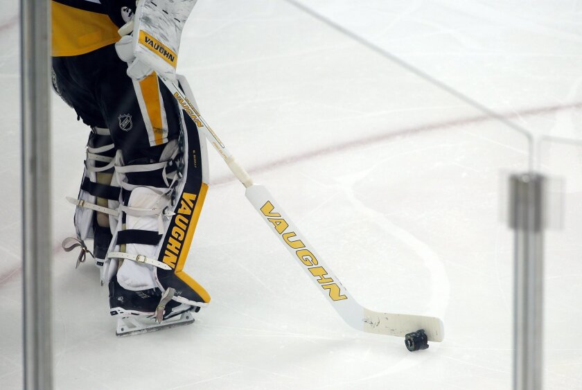 Pittsburgh Penguins goalie Matt Murray pushes a camera lens that landed on the ice during the first period in Game 2 of the NHL hockey Stanley Cup finals between the Penguins and the San Jose Sharks on Wednesday, June 1, 2016, in Pittsburgh. (AP Photo/Gene J. Puskar)