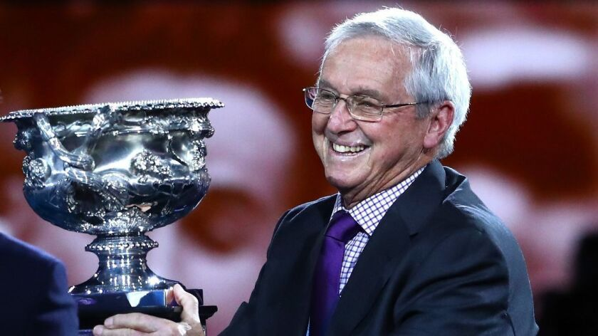 Roy Emerson poses with the Norman Brookes Challenge Cup before the men's singles final match at the 2019 Australian Open on Jan. 27.