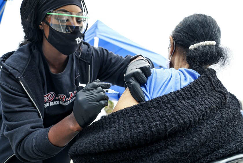 Janeen Williamson, with the San Diego Black Nurses Association, administers a vaccine to Olivetta Jones on Sunday.