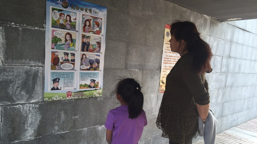 A mother and daughter look at a poster warning against foreign spies displayed at a riverside park in Beijing in April 2016.