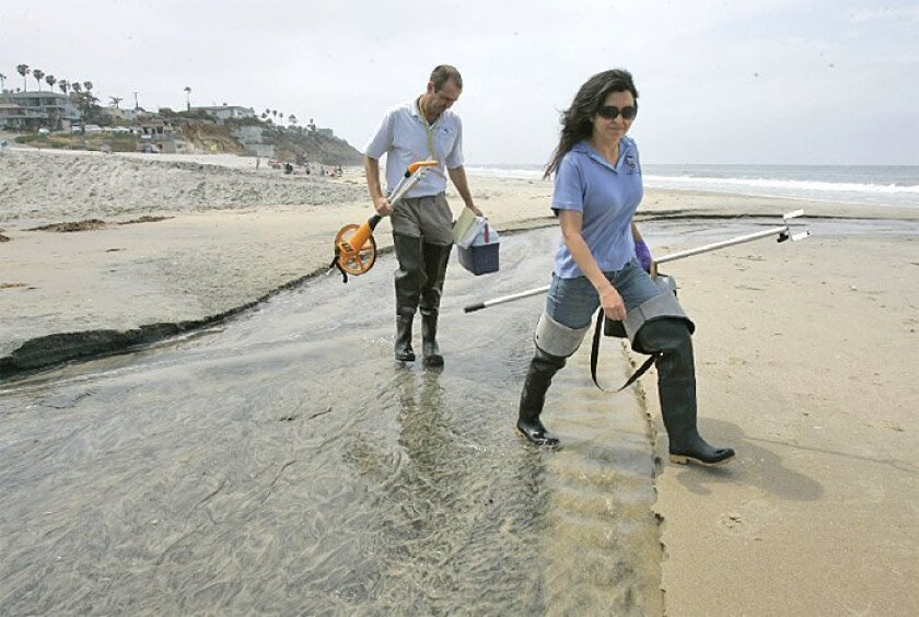 Mayela Padilla (right), an Encinitas city employee, and Ewan Moffat, a San Diego County worker, carried equipment to take water samples from the ocean near where Cottonwood Creek flows into the water at Moonlight Beach.  (Charlie Neuman / Union-Tribune)