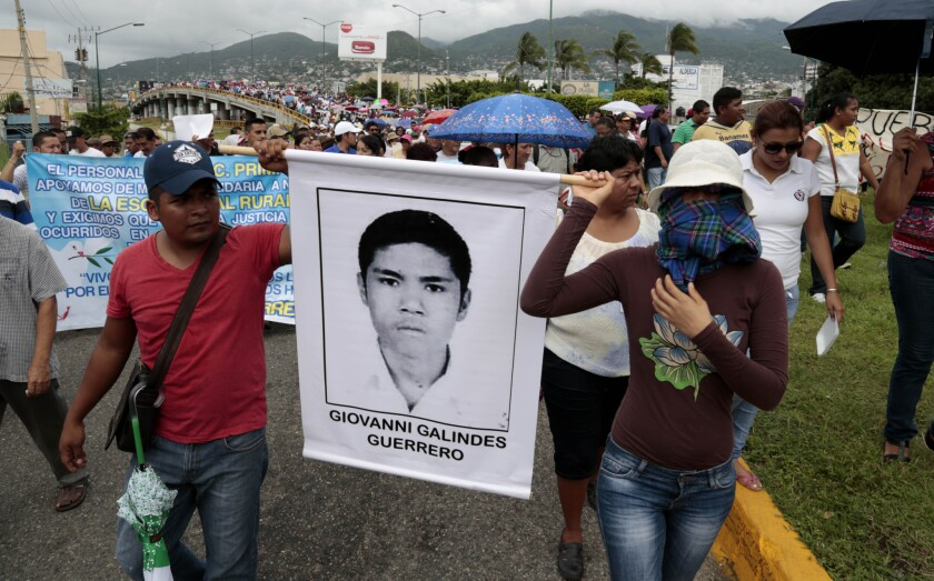 Masked demonstrators march with photographs of missing students to protest the disappearance of 43 students from the Isidro Burgos rural teachers college in Guerrero state, Mexico.