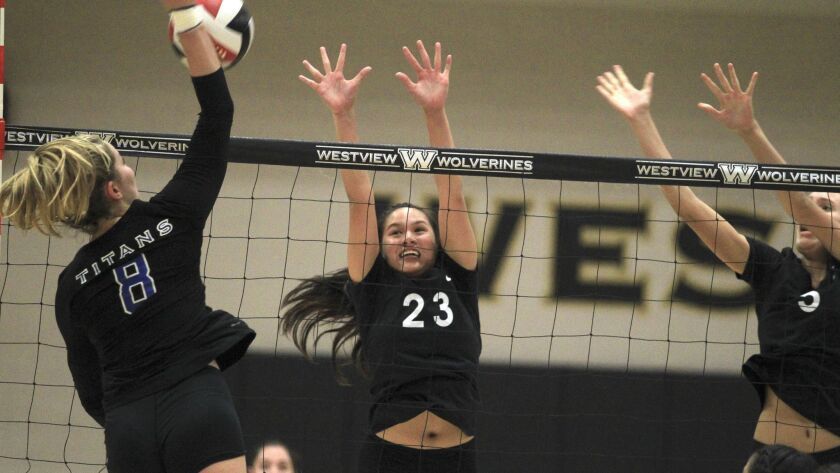 Westview's Lauryn de los Reyes (center) and Emilie Comer go up for a block against Eastlake's Madi Bogle Tuesday during the Division I semifinals. The host Wolverines won in five sets.