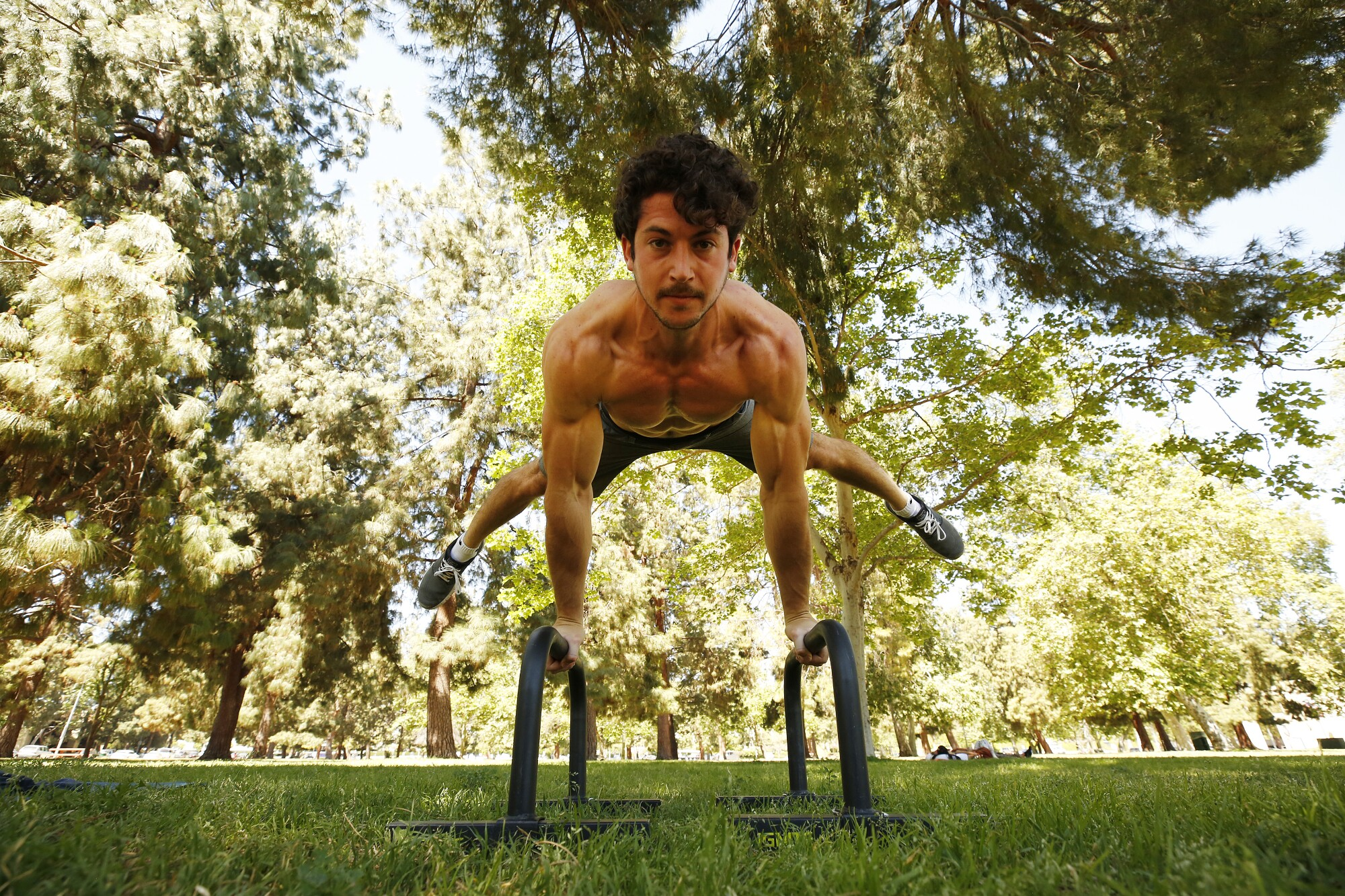 Personal trainer Yonatan Mishan works out in the shade at Warner Center Park in Woodland Hills.