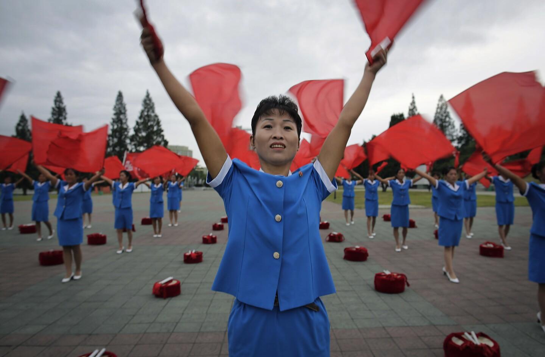 Mujeres norcoreanas ondean banderas saludando a sus compatriotas que están yendo a trabajar temprano en la mañana en Pyongyang, la capital de Norcorea. (AP Photo/Wong Maye-E)