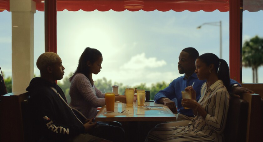 "Kelvin Harrison Jr., Taylor Russell, Sterling K. Brown and Renée Elise Goldsberry sit at a restaurant booth in ""Waves."""