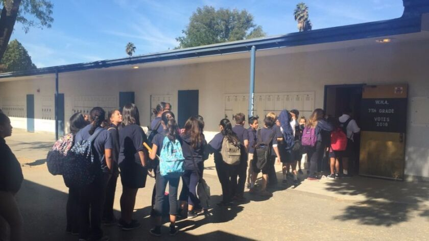 Students at Woodland Hills Academy line up outside their classroom to vote in a mock election.