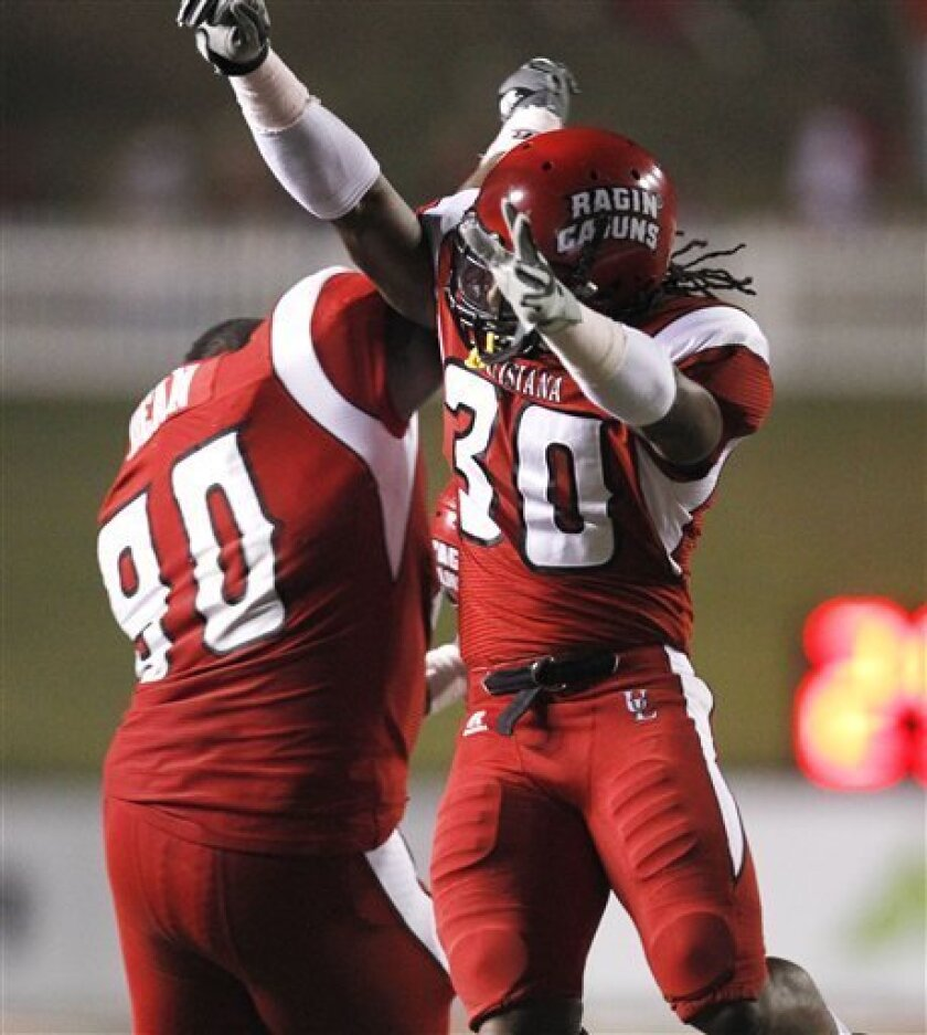Louisiana-Lafayette safety Le'Marcus Gibson (30) celebrates his interception with defensive tackle Derreck Dean (90) late in the second quarter of an NCAA college football game in Lafayette, La., Friday, Oct. 8, 2010. (AP Photo/Gerald Herbert)