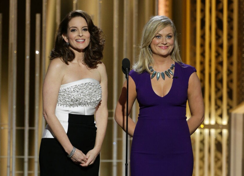 Tina Fey, left, and Amy Poehler speak during the 72nd Annual Golden Globe Awards.