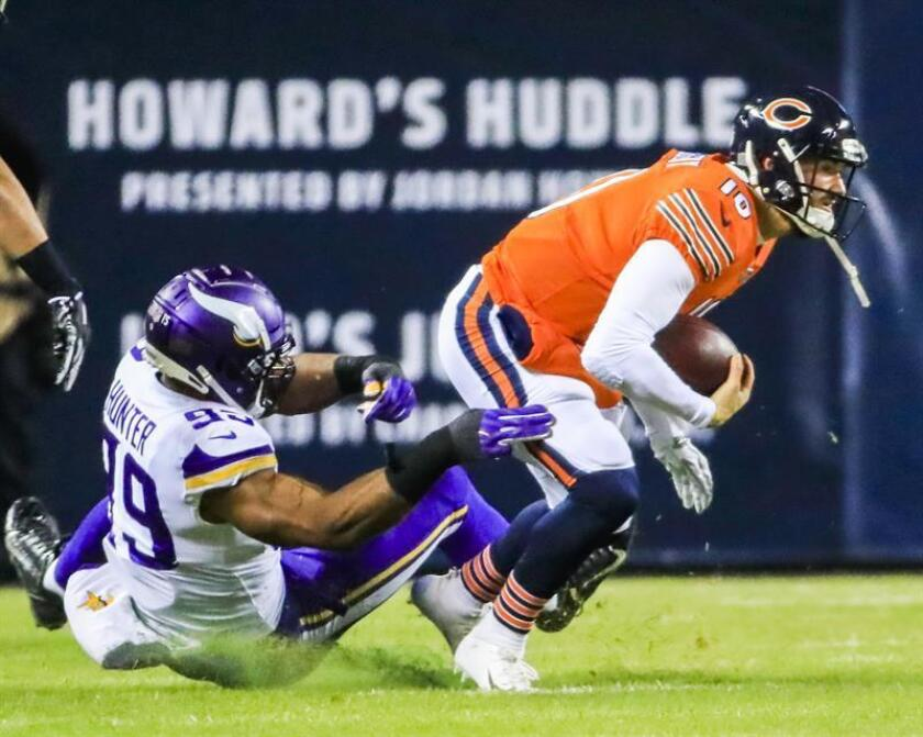 Chicago Bears quarterback Mitchell Trubisky (R) scrambles to escape the grasp of Minnesota Vikings defensive end Danielle Hunter (L) during the NFL game between the Minnesota Vikings and the Chicago Bears at Soldier Field in Chicago, Illinois, USA, Nov. 18, 2018. EPA-EFE/TANNEN MAURY