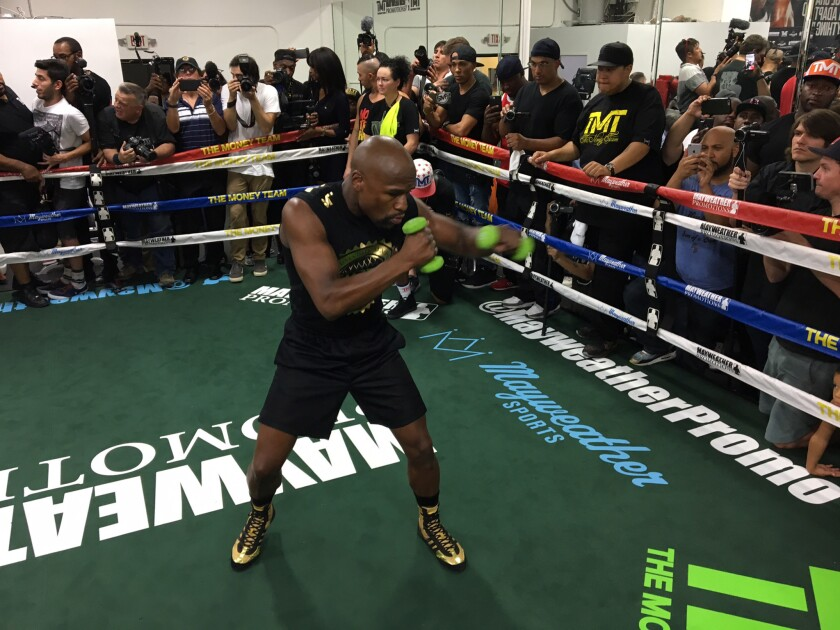 Floyd Mayweather does some shadow boxing with weights in his hands during his media workout.