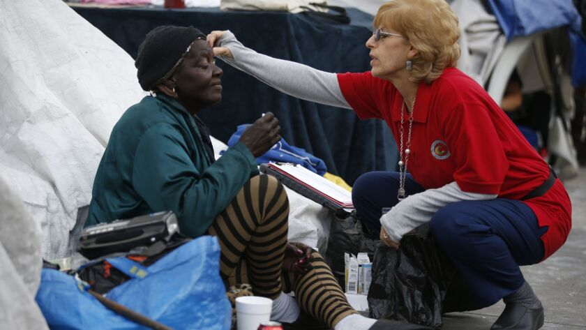 A nurse checks on a homeless woman on San Julian Avenue in downtown Los Angeles.