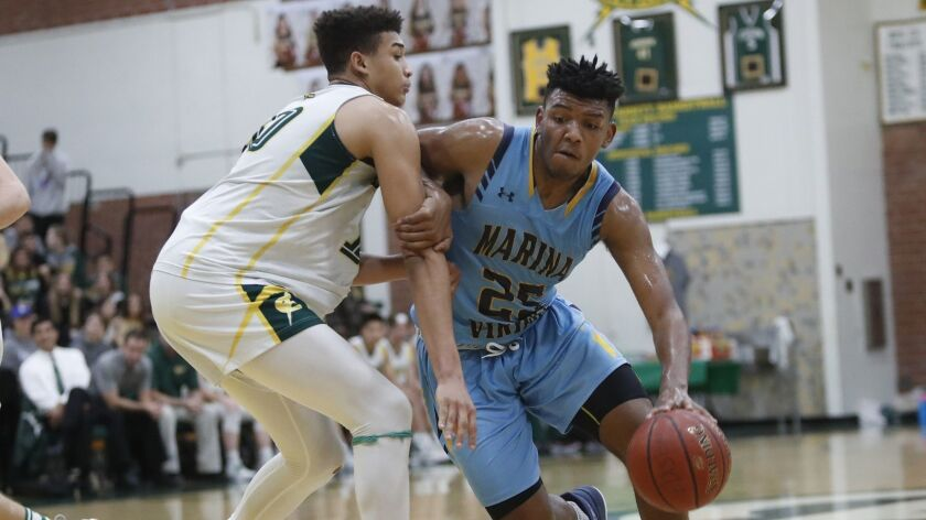 Marina's Jakob Alamudun drives to the hoop against Edison's Josh Phillips during a Sunset League gam