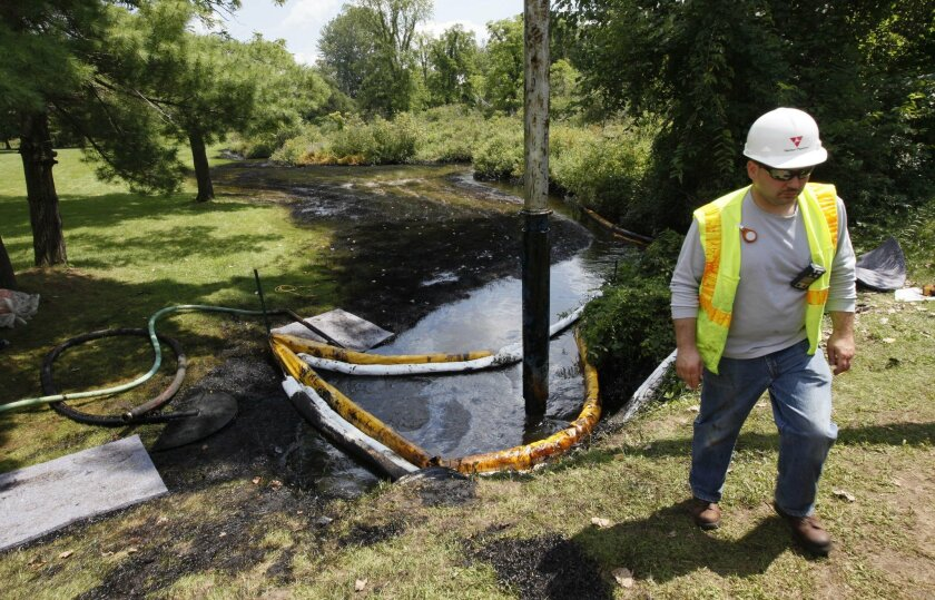 FILE - In this July 29, 2010 file photo, a worker monitors the water in Talmadge Creek in Marshall Township, Mich., near the Kalamazoo River as oil from a ruptured pipeline, owned by Enbridge Inc, is vacuumed out the water. Enbridge Energy Partners will pay a $61 million penalty for the costliest i