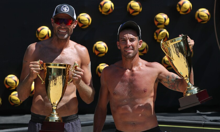 Phil Dalhausser, left, and Nick Lucena celebrate their victory at the AVP tournament in Long Beach on Juky 26, 2020.