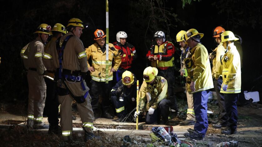 Firefighters search for a Jesse Hernandez, 13, in a hole near the Los Angeles River at the interchange of the 134 and 5 freeways on Sunday night.