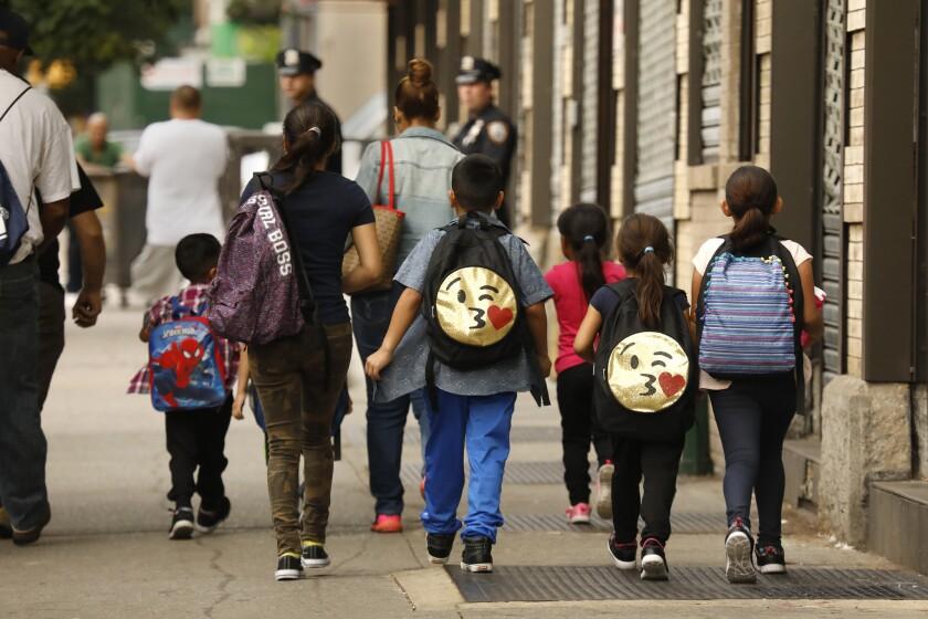 Children wearing backpacks walk together along a New York sidewalk.