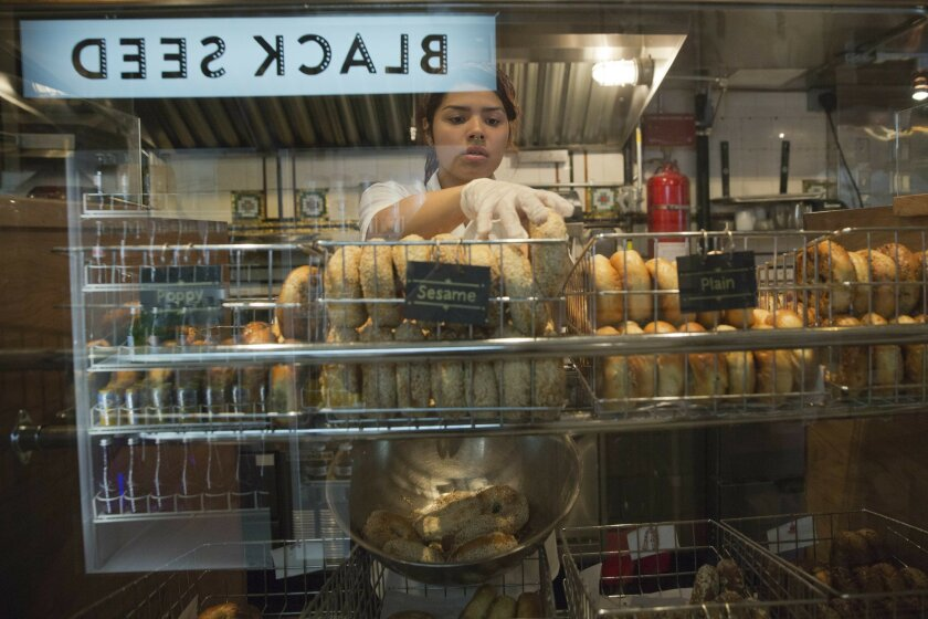 An employee of the Black Seed bagel shop arranges freshly baked bagels on the store's display in the East Village neighborhood of New York on Friday, May 27, 2016. (AP Photo/Mary Altaffer)