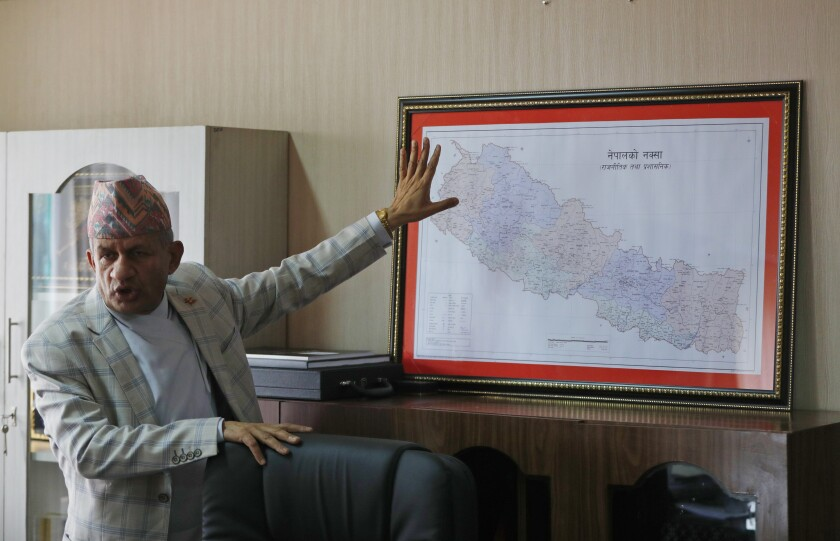 FILE - In this Tuesday, June 9, 2020, file photo, Nepal's Foreign Minister Pradeep Gyawali points to a map of Nepal during an interview with the Associated Press in Kathmandu, Nepal. Nepal's parliament overwhelmingly approved a constitution amendment on Saturday to change the nation's map that includes territory claimed by both Nepal and India which is likely to anger New Delhi. House of Representatives speaker Agni Kharel announced that all 258 members who were present on Saturday voted in favor of the constitution amendment proposal. The amendment proposal needed two-third of the 275 total seats in the parliament. (AP Photo/Niranjan Shrestha, File)