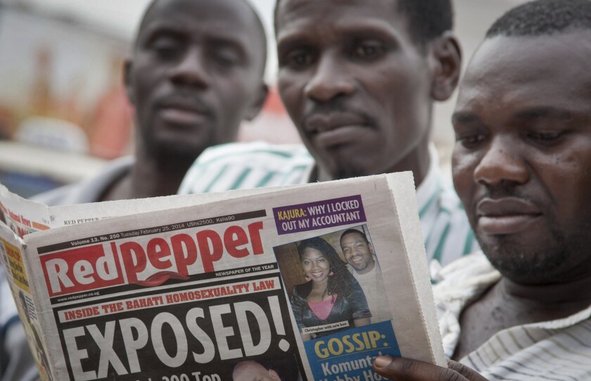 "Ugandans read a copy of the Red Pepper newspaper in Kampala on Tuesday. It published a list of what it called the country's ""200 top"" homosexuals, outing some Ugandans who previously had not identified themselves as gay, one day after President Yoweri Museveni enacted a harsh anti-gay law."