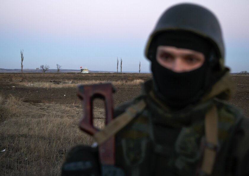 FILE - In this Saturday, Feb. 21, 2015, file photo, a Russia-backed rebel guards a bus of Ukrainian war prisoners in a field, near Zholobok, Ukraine. AP reporting, based on dozens of conversations with rebel fighters and visits to their training grounds, has revealed the extent of the involvement o