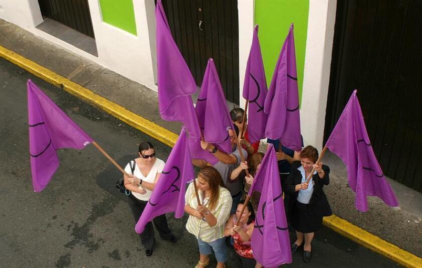 El personal de la Oficina Procuradora de las Mujeres marcha el miércoles 2 de noviembre por las calles del Viejo San Juan portando dieciséis banderas violetas para llamar la atención sobre la violencia contra las mujeres en el país, tras el asesinato de Socorro del Pilar Cosme Torres ayer, martes, en Naranjito (Puerto Rico). EFE/Archivo