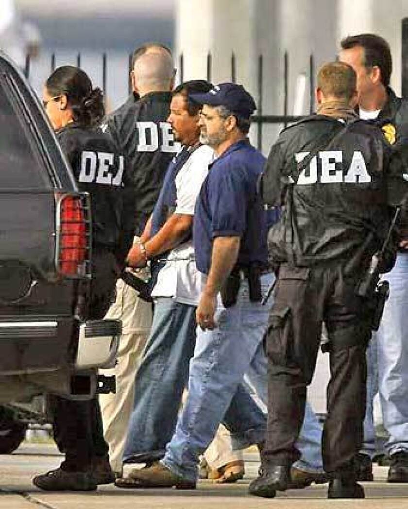 U.S. DEA agents escort a suspect taken from the U.S. Coast Guard ship Monsoon to a waiting vehicle at Coast Guard station San Diego.