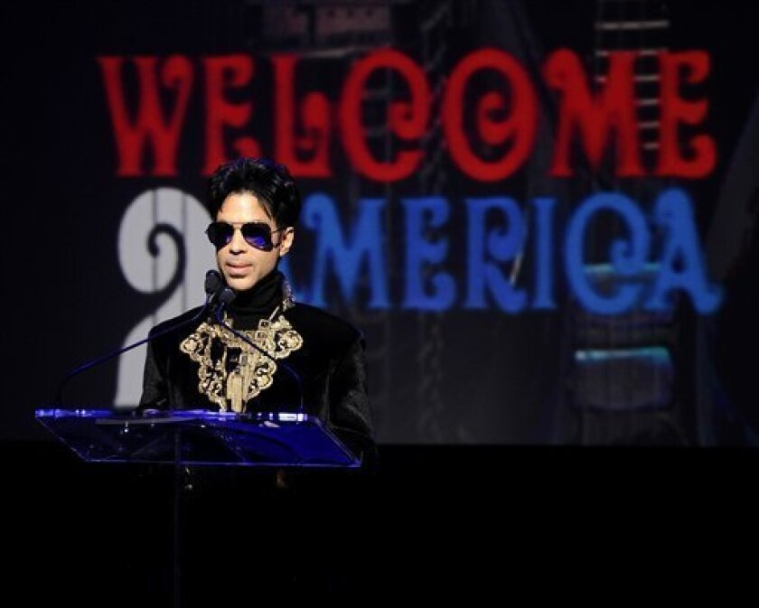 "FILE - In this Oct. 14, 2010 file photo, musician Prince holds a news conference at The Apollo Theater announcing his ""Welcome 2 America"" tour in New York. Prince turns off the lights at South by Southwest on Saturday night, Match 16, 2013, with an unexpected and intimate showcase that ranks among"