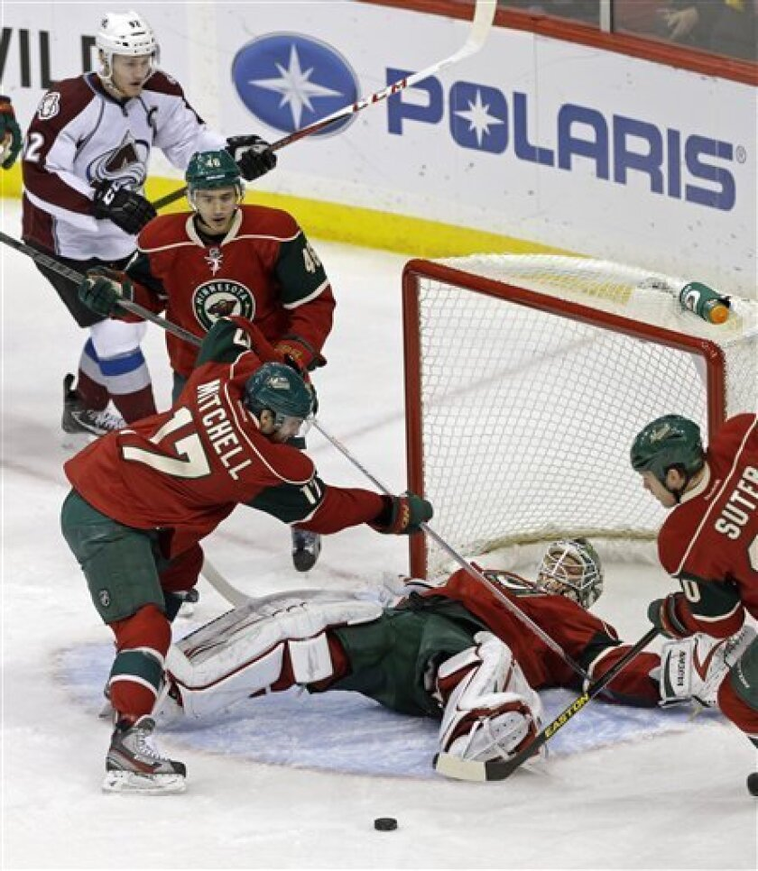 Minnesota Wild's Torrey Mitchell, left, and Ryan Suter, right, come to the aid of goalie Niklas Backstrom, of Finland, after he fell while protecting the net, as Colorado Avalanche's Gabriel Landeskog of Sweden, top left, skates in during the first period of an NHL hockey game Thursday, March 14, 2