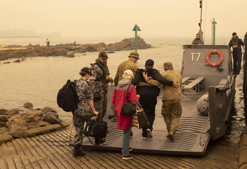 Evacuees board landing craft
