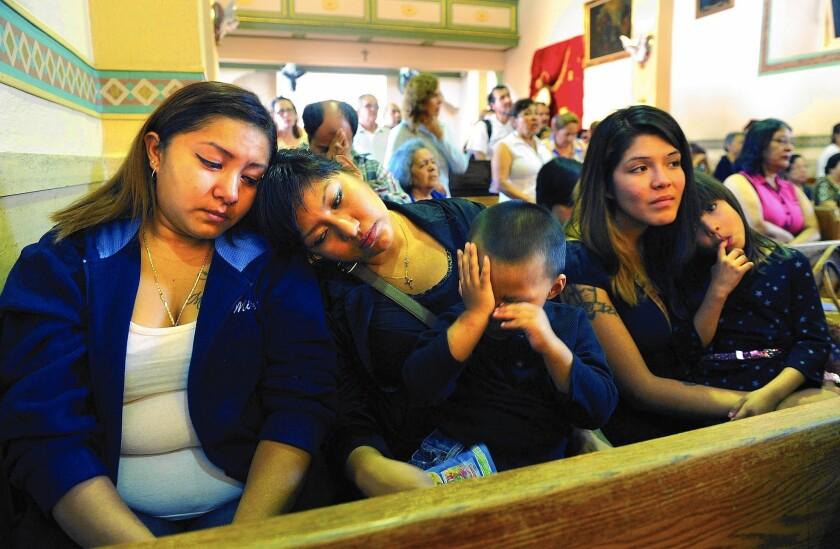 Karina Valenzuela, left, next to her sister Lissette Arreola, and other family members attend a Mass for Gloria Ortiz.