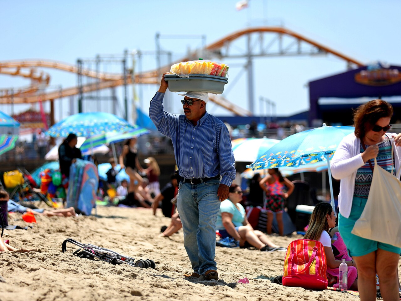 A vendor sells fruit to beachgoers in Santa Monica. Some licensed vendors working around the pier say a new ordinance that can penalize them for blocking access ways has made them nervous about being arrested.