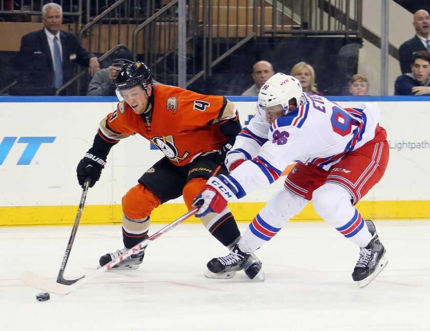 Ducks defenseman Cam Fowler (4) tries to hold off Emerson Etem (96) of the Rangers as he pursues the puck during a game on Dec. 22, 2015.