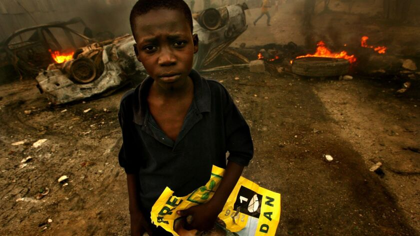 A young Haitian holds a rock and a poster of presidential candidate Rene Preval in front of a burning barricade. Violence broke out after a delay in election results.