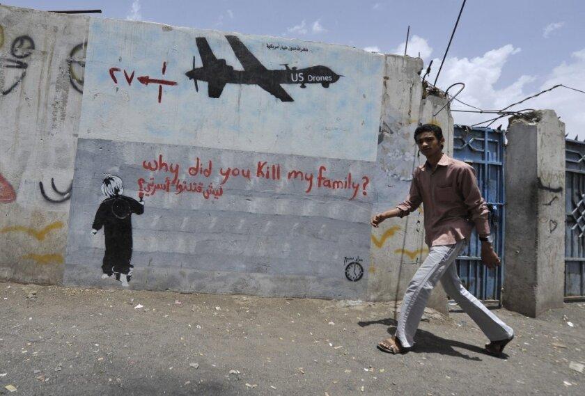 A man walks near graffiti protesting U.S. drone operations in Yemen last April.