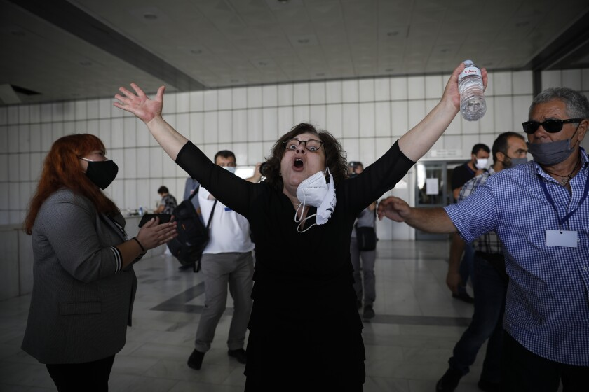Magda Fyssa, whose son was killed by a Golden Dawn supporter in 2013, throws up her arms in celebration after court ruling