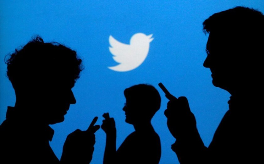 FILE PHOTO: People holding mobile phones are silhouetted against a backdrop projected with the Twitter logo in this illustration picture taken September 27, 2013.