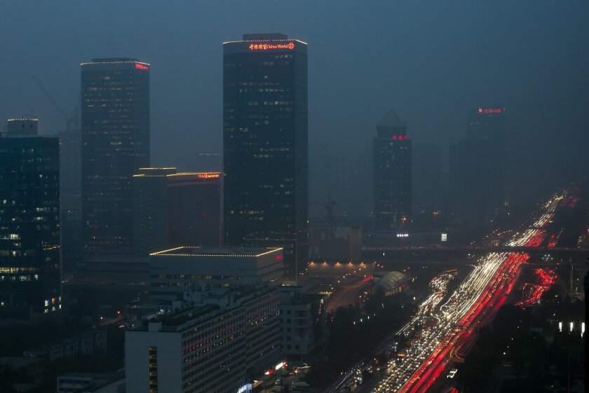 In this photo taken with a slow shutter speed, buses and cars are clogged with heavy traffic on Chang'an Avenue shrouded with haze pollution in Beijing Thursday, Sept. 24, 2015. (AP Photo/Andy Wong)