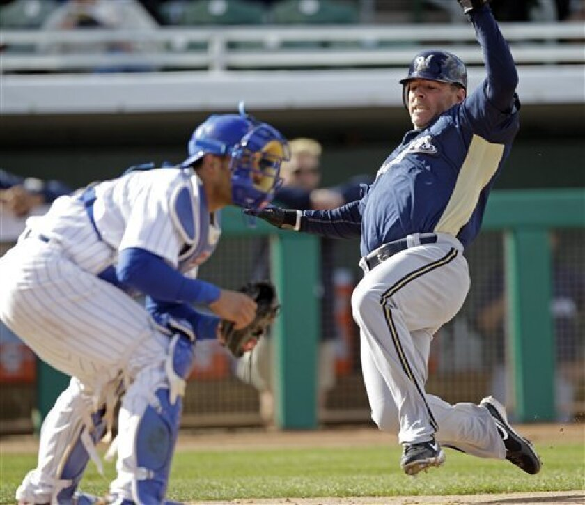 Milwaukee Brewers' Jim Edmonds scores past Chicago Cubs catcher Geovany Soto on a hit by Jody Gerut during the fifth inning of a spring training baseball game Tuesday, March 9, 2010, in Mesa, Ariz. (AP Photo/Morry Gash)