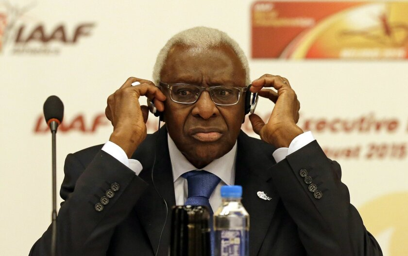 FILE - In this Aug.21, 2015 file photo, then IAAF president Lamine Diack adjusts his headphones during a joint IOC and IAAF press conference on the side of the World Athletic Championships in Beijing. The French office that handles financial prosecutions says Wednesday Nov.4, 2015 Diack has been pl