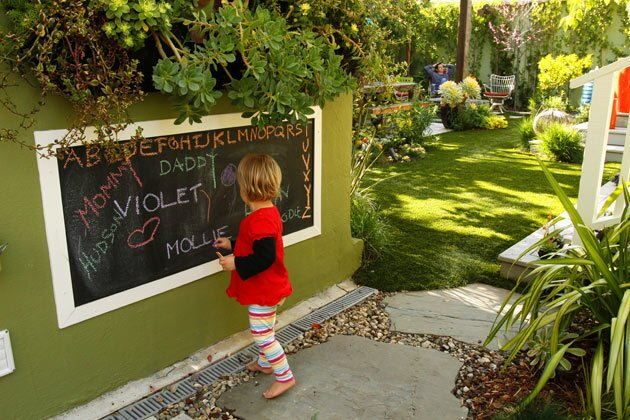 By Lisa Boone For proof that parenthood does change everything, just look at the Mar Vista garden of landscape designer Elizabeth Low. The birth of daughter Violet, now 2, inspired her to consider the question: How would the arrival of a child change the landscape. Here's a peek at Low's garden transformation and how the outdoor areas now serve as an extension of the 900-square-foot house. Pictured here: Low's daughter, Violet Cash, 2, draws on the outdoor chalkboard designed by her mother, who rolled chalkboard paint onto the wall and added a painted wood frame. The girl's father, David Cash, is in the background, by the fire pit.