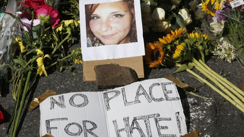 A makeshift memorial of flowers and a photo of victim, Heather Heyer, sits in Charlottesville, Va.,