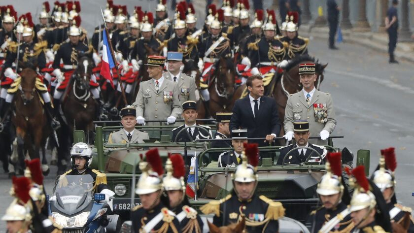 France's President Emmanuel Macron and Chief of Staff of the French Army General Francois Lecointre stand in the command car as they drive down the Champs-Elysees during the Bastille Day parade in Paris on Sunday.