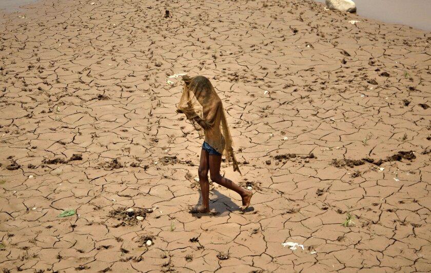 En esta fotografía de archivo, un joven indio se cubre la cara para protegerse del calor mientras camina en una cama seca del río Tawi un caluroso día de verano en Jammu, India. Funcionarios de India lanzarán un programa para proteger a las personas del calor extremo en dos regiones de alto riesgo, después de que una devastadora ola de calor matara al menos a 2.500 personas alrededor del país el año pasado. (Foto AP/Channi Anand, Archivo)